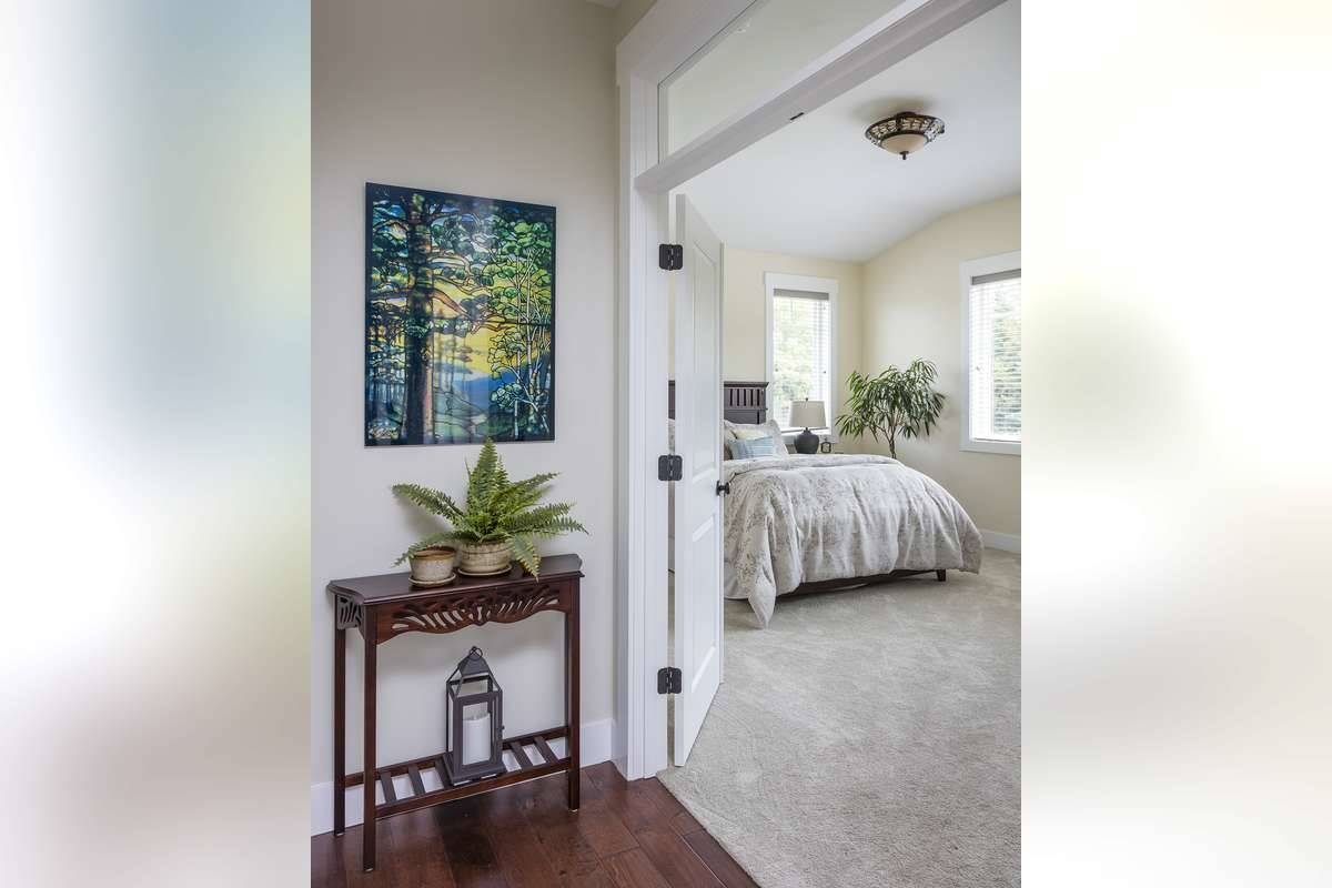 The primary suite has carpet flooring, beige walls, and a vaulted ceiling mounted with a semi-flush light.