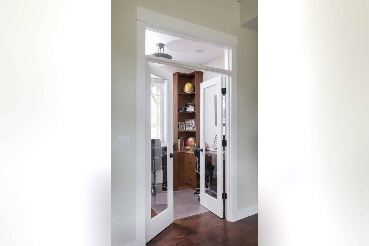 A white french door opens to the home office that comes with wooden built-ins and desks.