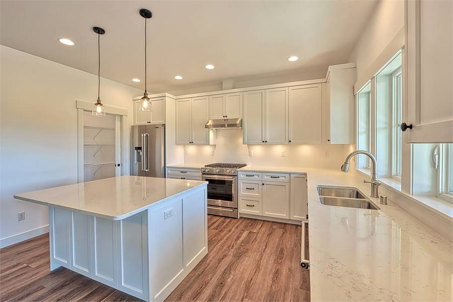 The kitchen is equipped with stainless steel appliances, white cabinetry, a double bowl sink, marble countertops, and a center island.