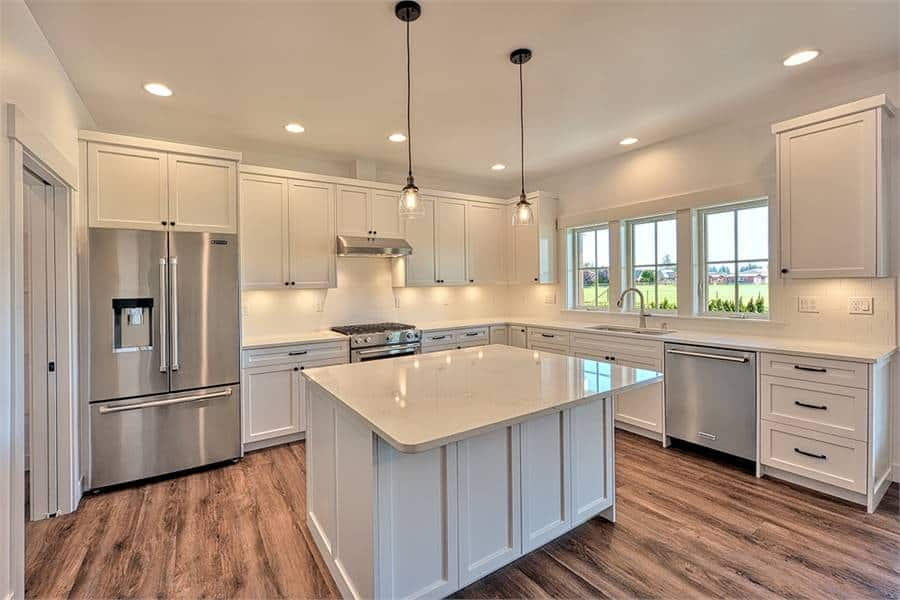 Recessed ceiling lights along with a pair of glass pendants create a warm ambiance to the kitchen.