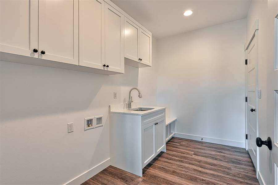 The laundry room has a washstand and white overhang cabinets with wrought iron knobs.