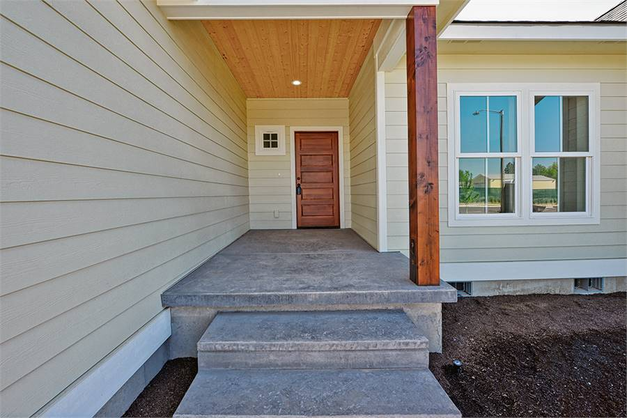 A closer view of the front porch showing the concrete stoop and a wooden entry door.