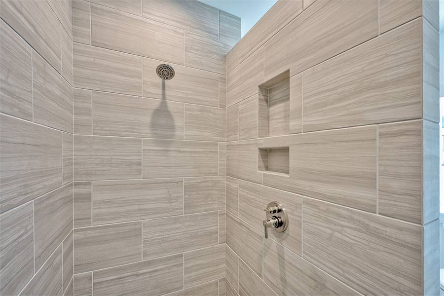 Walk-in shower with chrome fixtures, tiled walls, and inset shelves.