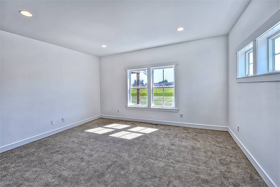 This spare room with a white framed window and carpet flooring is dedicated to the primary suite.