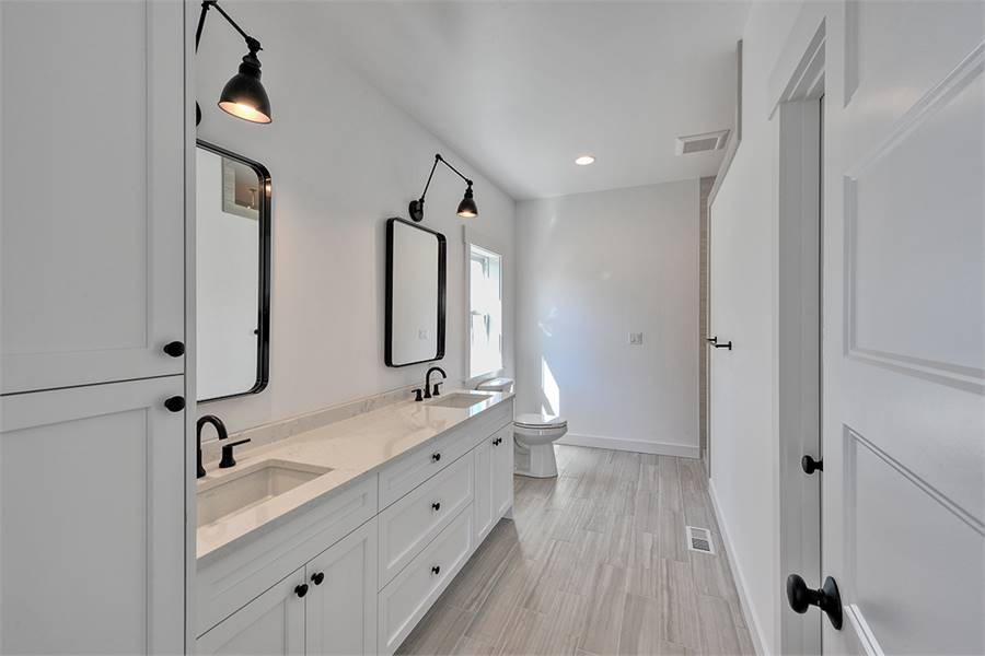 The primary bathroom has a toilet and a dual sink vanity paired with framed mirrors.