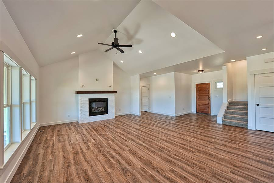 Spacious living room with a glass-enclosed fireplace and a vaulted ceiling mounted with a fan.