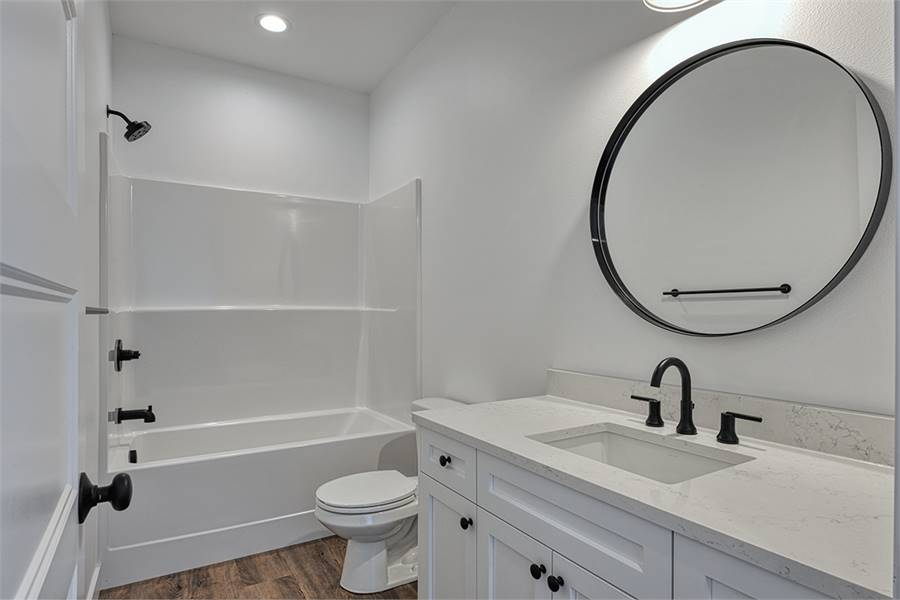 This bathroom is equipped with white vanity, a toilet, and a shower and tub combo.