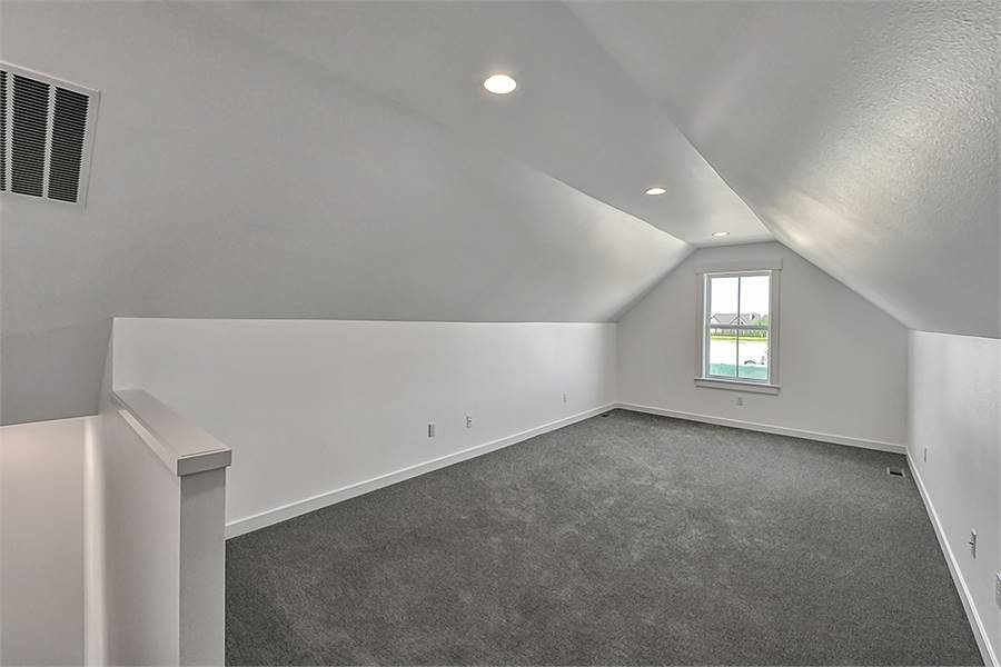 Bonus room with a single window and vaulted ceiling fitted with recessed lights.