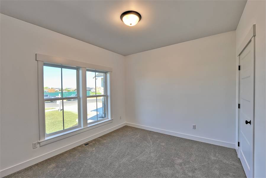 This bedroom has carpet flooring, white walls, and a regular ceiling mounted with a flush light.