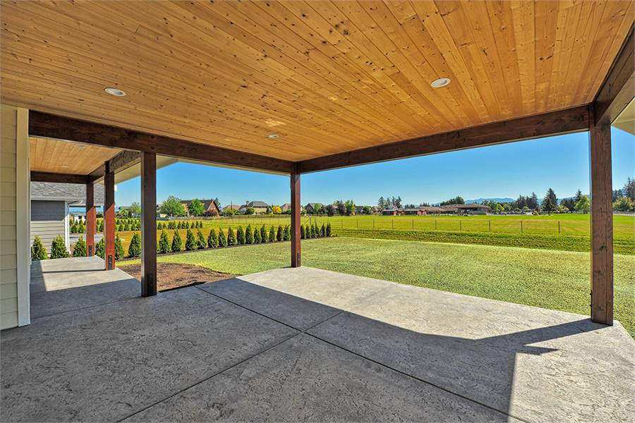 The rear patio has concrete flooring and wood-paneled walls.