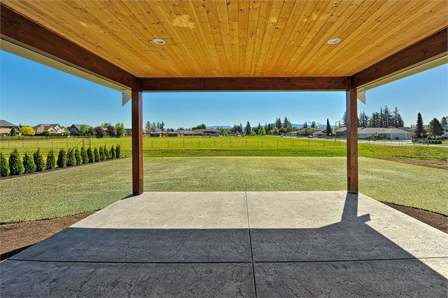 An expansive view of the lush green lawn can be seen from the covered patio.