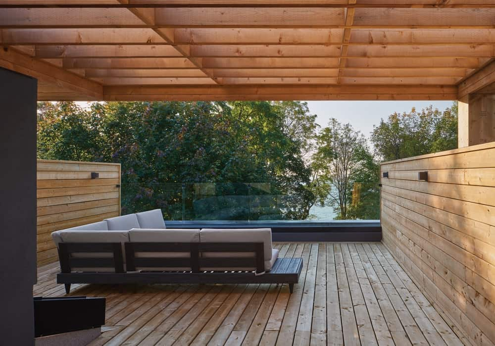 This is the wooden deck terrace of the house with shiplap walls, floor and trellises above the L-shaped sofa.