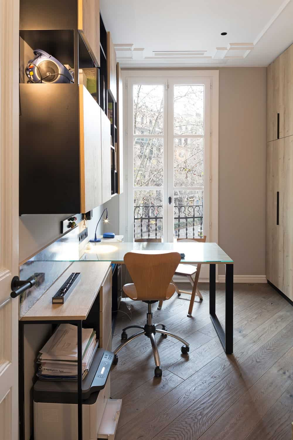 Across from the sofa is this L-shaped office desk paired with a modern office chair facing a set of Fremch doors leading to a balcony.