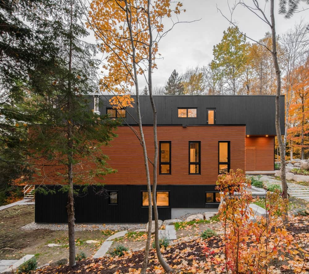 The house is surrounded by natural landscape of rocks and trees making the straight lines and warm lighting stand out.