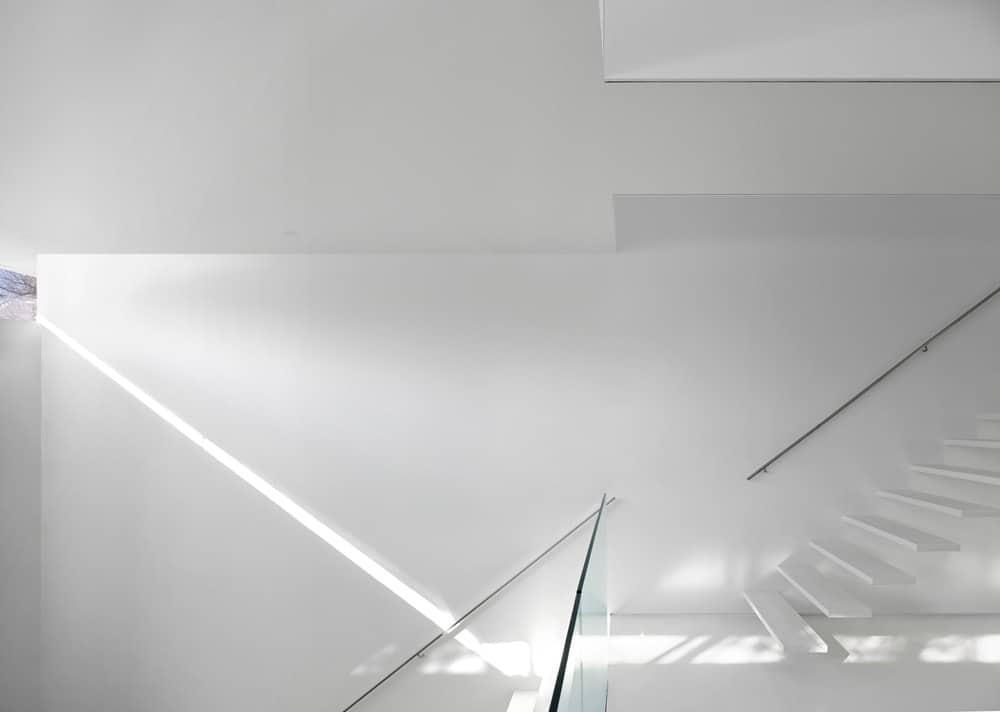 This is a view of the ground level landing with white modern stairs and glass railings complemented by the natural light.