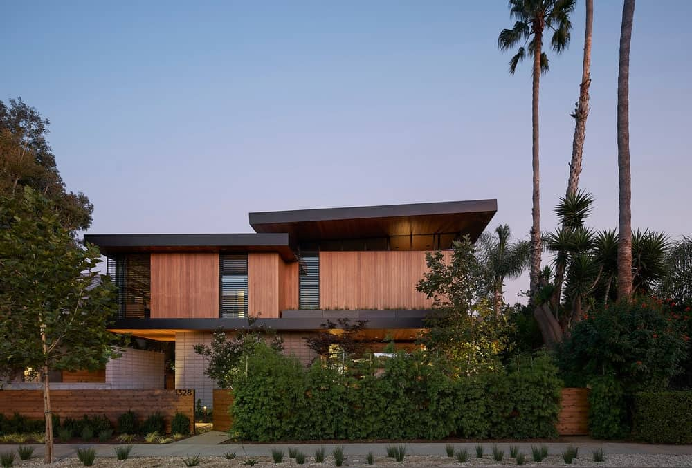 This is a view of the front of the house that has wooden tones on its exteriors adorned by the shrubs in front of the house.