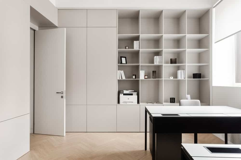 This is a far view of the office showing the large dark desk that stands out against the same light beige tone of the rest of the office.