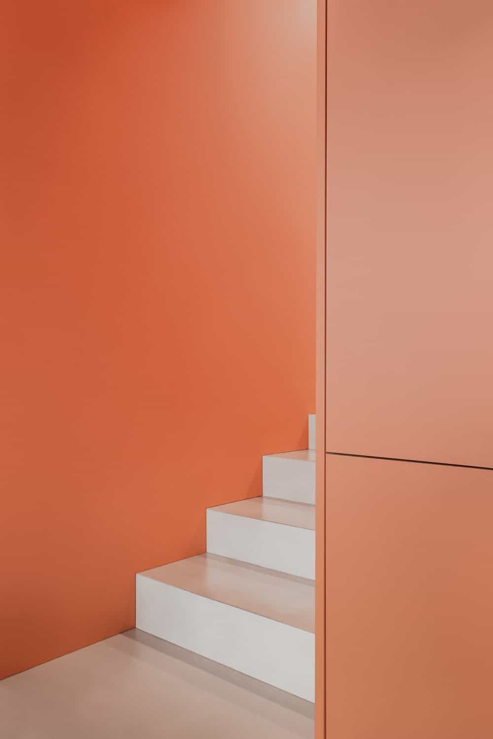 This is a look at the light gray steps of the staircase that is contrasted by the matte orange wall panels.