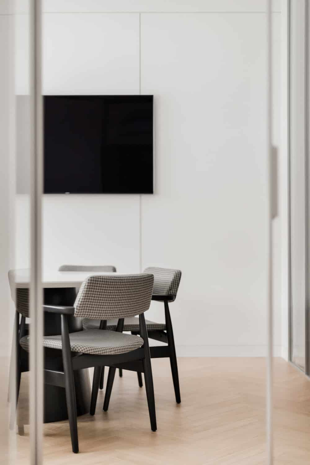 The conference room next room has a large wall-mounted TV that stands out against the light beige wall.