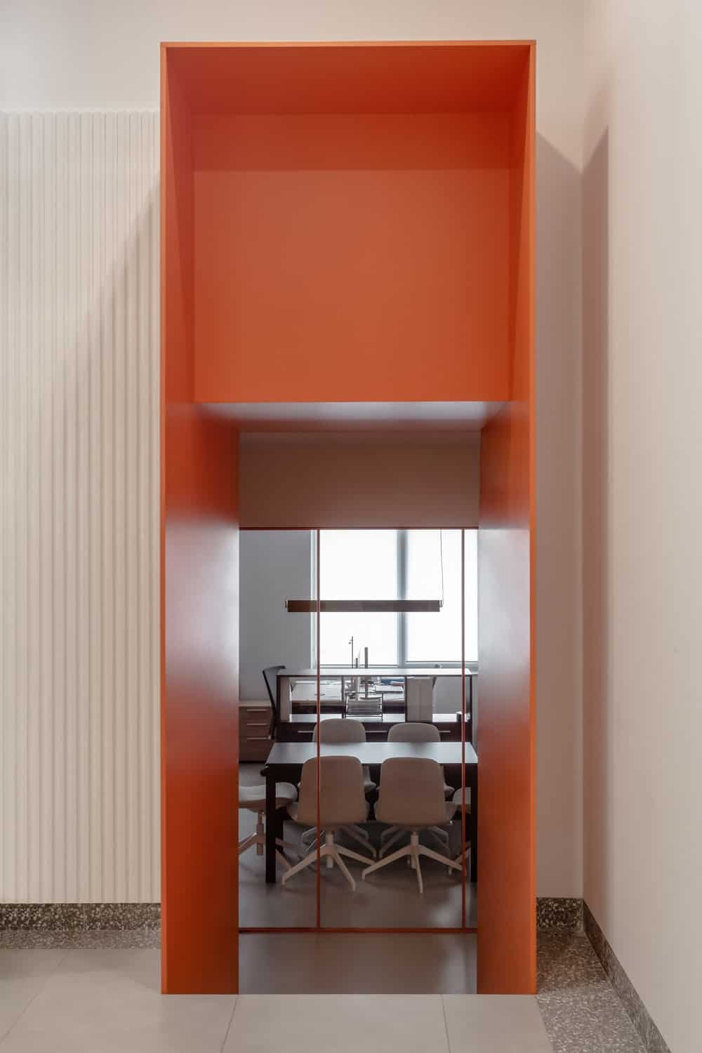 This is a look at the orange entryway that leads to more office space with large wooden conference table and desks at the far side.