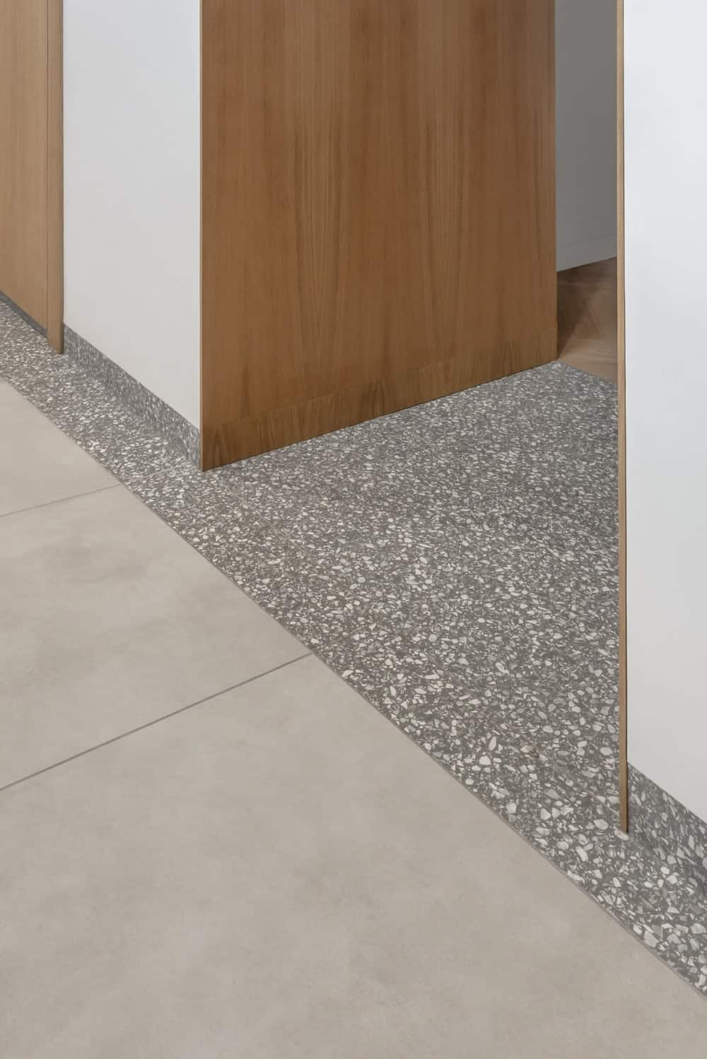 This is a close look at the foot of the hallway with a patterned gray floor contrasted by the wood-toned panel of the wall.