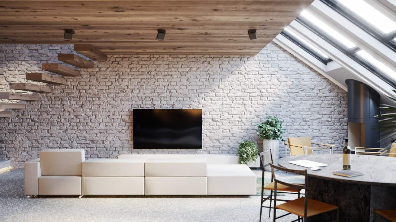 This is a close look at the living room area with a large beige sectional sofa across from a large red brick wall with a wall-mounted TV.