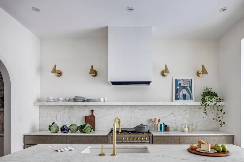 The kitchen has a consistent light beige tone with open shelves and a large kitchen island of the same light beige tone.