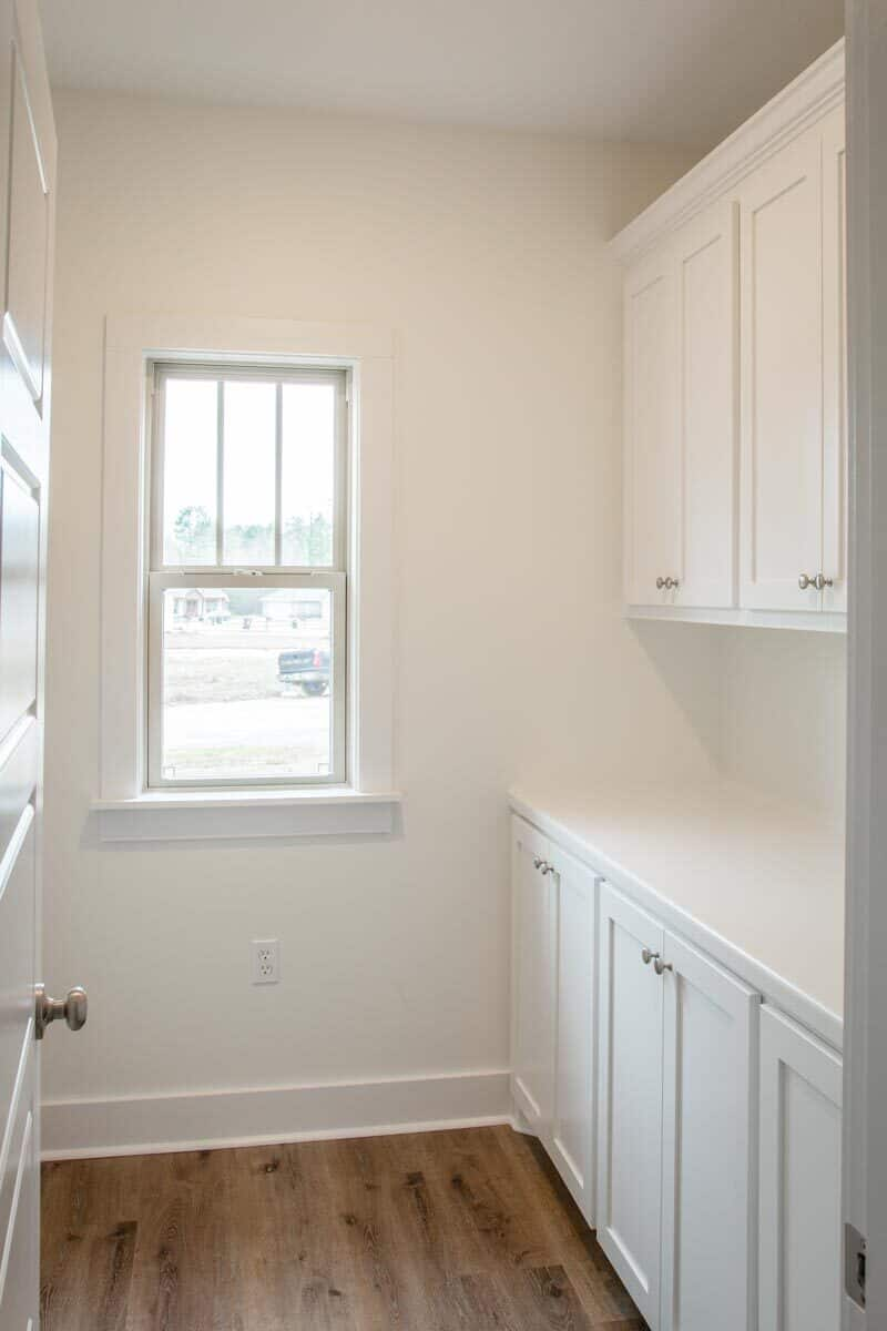 The walk-in pantry is filled with white cabinets and a quartz countertop.
