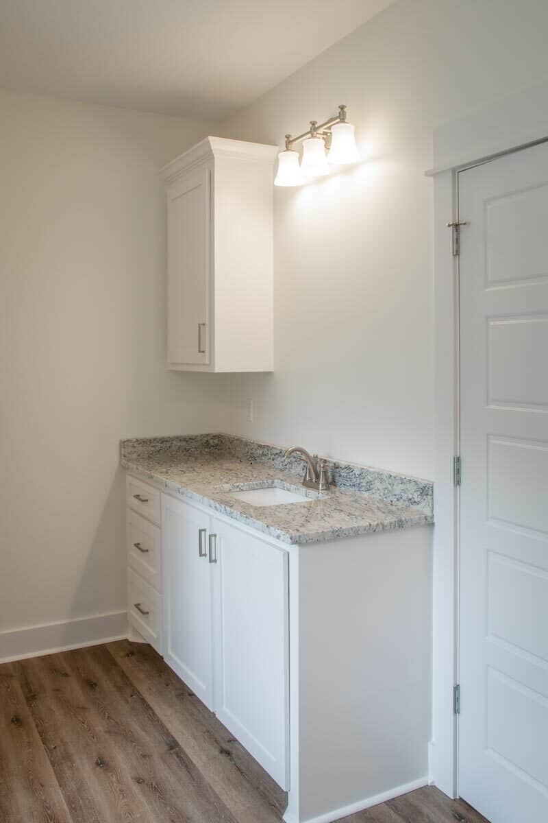 Utility room with white cabinets and an undermount sink fitted against the granite countertop.