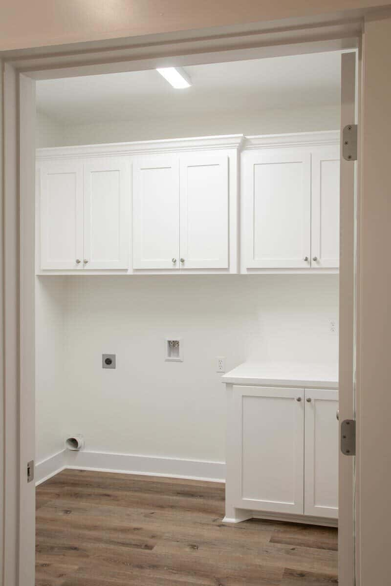 The built-in cabinets blend in with the white walls that are lined with base molding.
