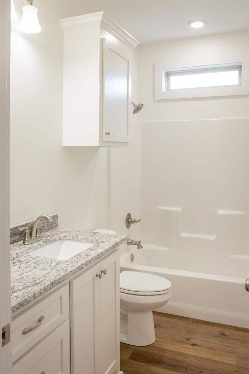 The bathroom is equipped with a sink vanity, a toilet, and a shower and tub combo.