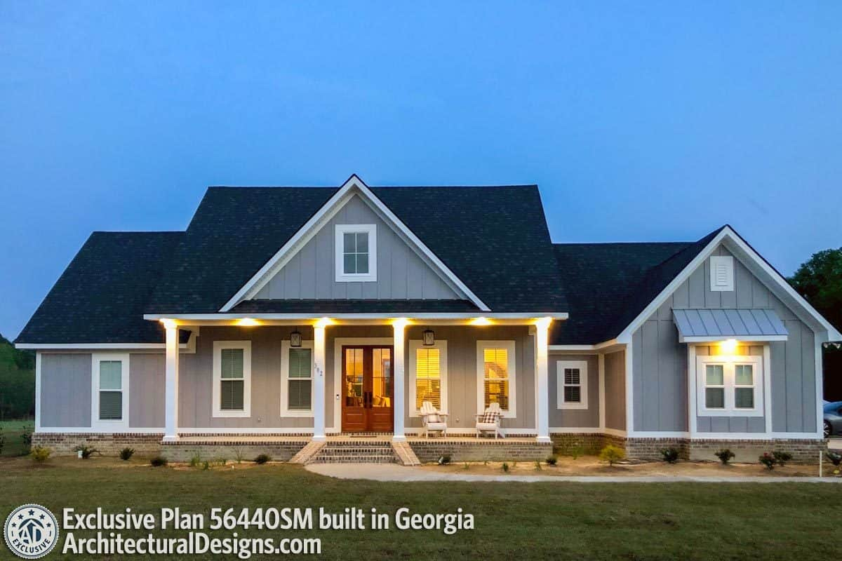 This home showcases a gray board and batten siding, white columns, and brick bases.