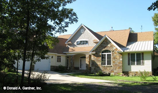 Front exterior view showing the arched entry porch and the angled garage.