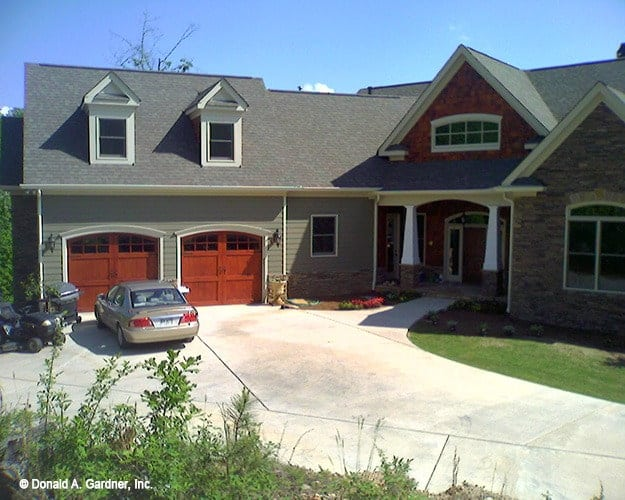 An alternate exterior showcasing gray siding, stone accents, and redwood garage doors.