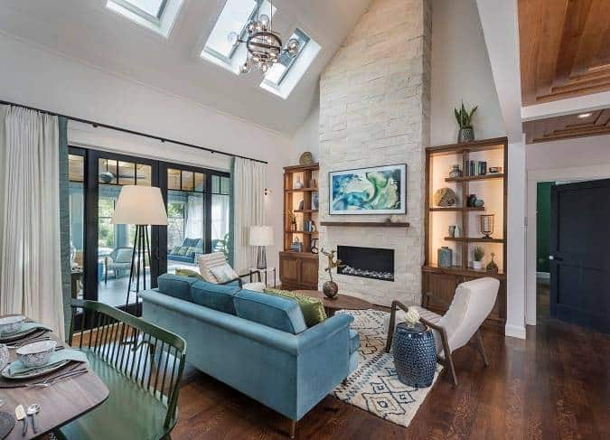 The living room has a blue velvet sofa, cushioned chairs, an oval coffee table, and a modern fireplace flanked by wooden built-ins.