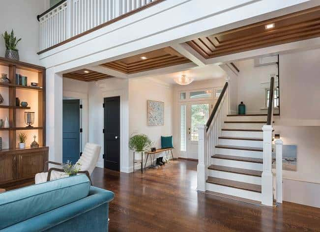 The staircase sits next to the foyer that showcases a glazed entry door and a wooden bench adorned with a teal pillow and artwork.
