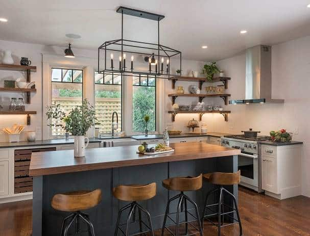 Kitchen with white cabinets, wooden floating shelves, and a center island well-lit by a linear chandelier.
