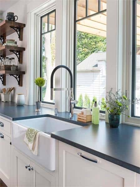 A closeup look of the farmhouse sink paired with a gooseneck faucet. Glass panel windows on top bring in an abundance amount of natural light.
