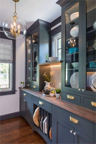 Display cabinet in charcoal with brass and chrome hardware. It is illuminated by a glass pendant hanging from the regular ceiling.