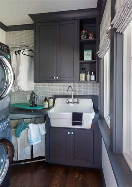 Utility room with gray cabinets, a farmhouse sink. and front load appliances.