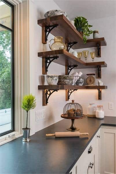 The corner shelves fixed above the white cabinets are filled with glassware and decors.