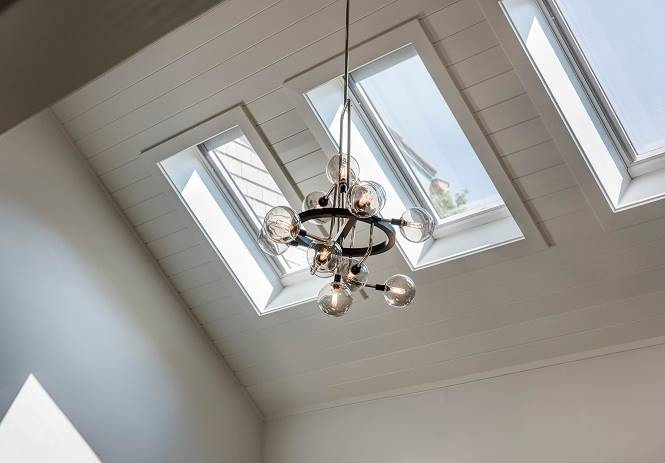The vaulted ceiling is fitted with skylights and a contemporary chandelier.