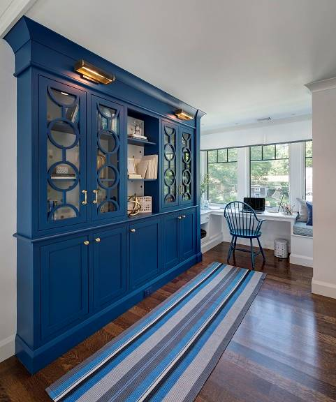 Library loft with a blue bookcase, a striped runner, and a built-in desk attached to a window seat.