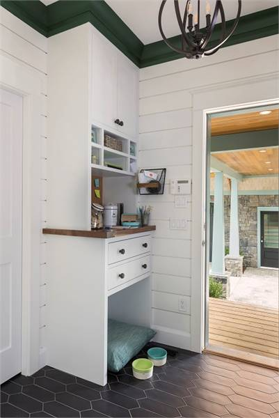 The mudroom has white built-ins and shiplap walls lined with green crown molding.
