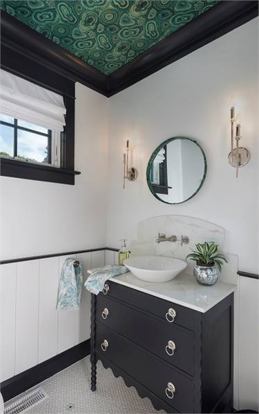 Powder room with a decorative ceiling and a vessel sink vanity paired with a round mirror.