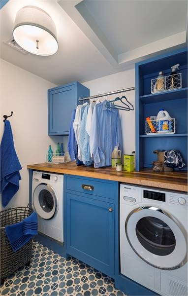 Laundry room with white front-load appliances, blue cabinets, and patterned tile flooring.