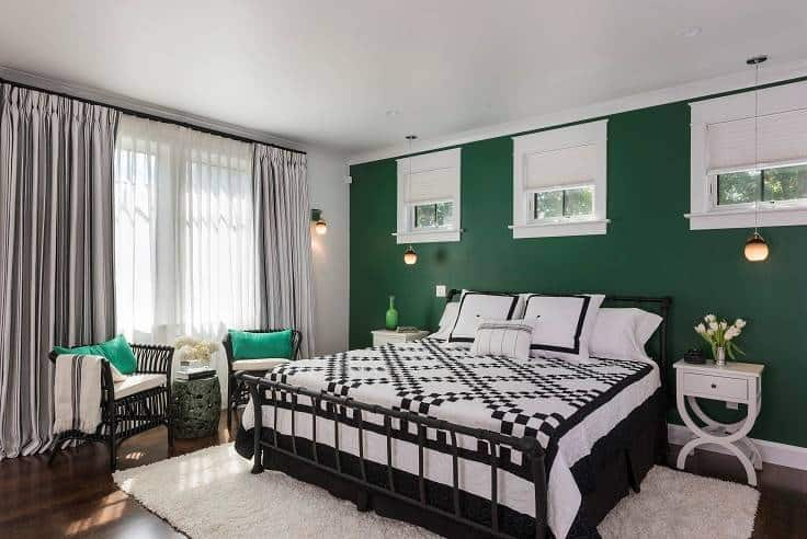 Another bedroom with a green accent wall and a sitting area by the floor-to-ceiling windows.
