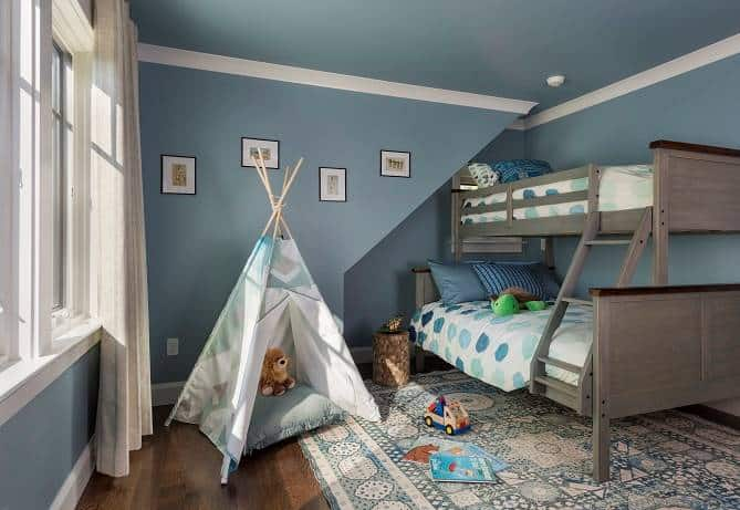 This bedroom offers a bunk bed, a large patterned rug, and a teepee tent perfect for kids.