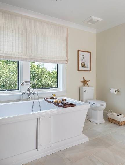 Next to the soaking tub is a toilet topped with a wooden framed artwork.