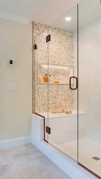 The walk-in shower has a mosaic tile accent wall, an inset shelf, a built-in seat, and a glass hinged door.